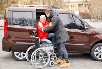 man assisting a senior man getting off the van