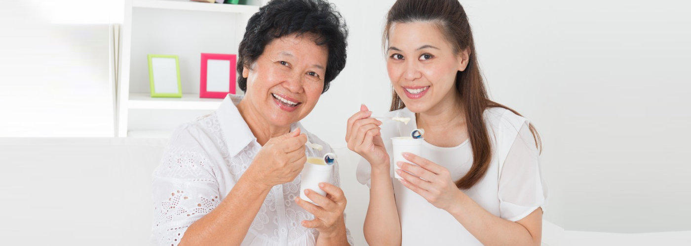 caregiver and a senior woman eating snacks
