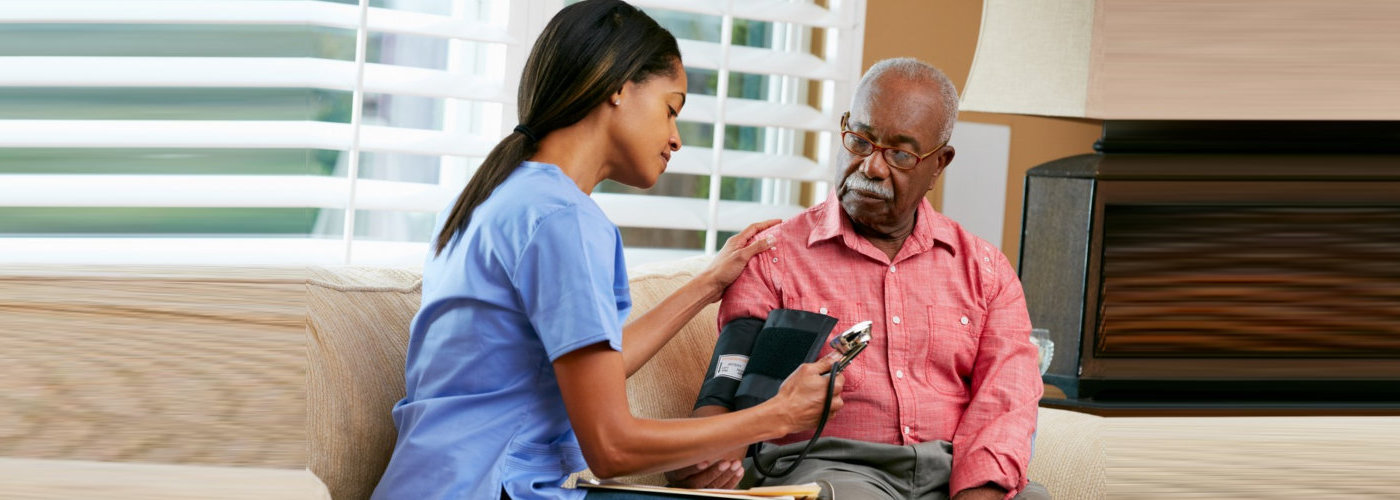 caregiver checking the bloodpressure of a senior man